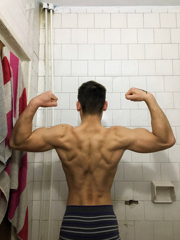 Back view of man flexing while in bathroom