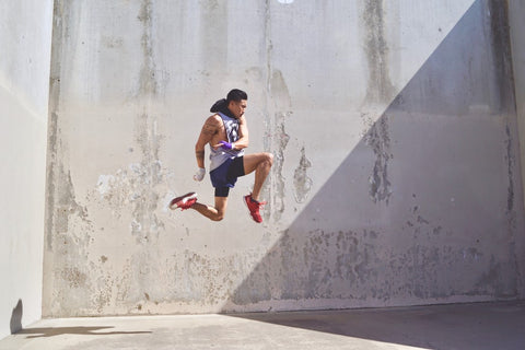 Man Jumping very high in front of stone wall