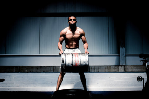 Man lifting heavy keg in spotlight during workout