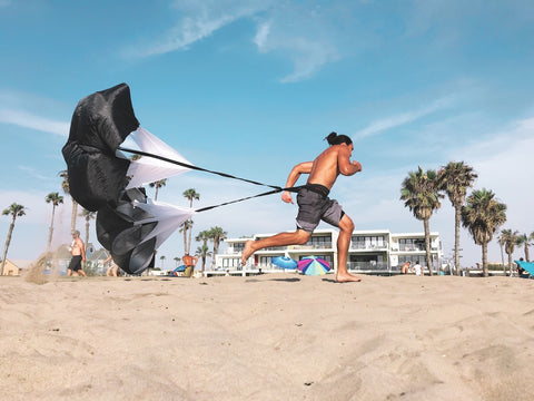 Man running with resistance parachute on beach