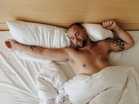 Man sleeping in bed with arms spread out