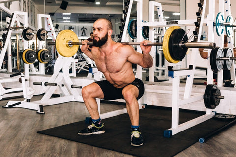 Man squatting with barbell on back in gym