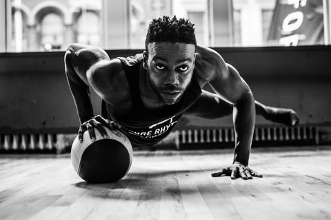Man in plank with one hand on medicine ball