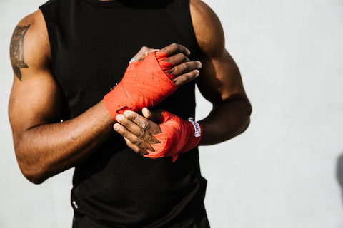 Man putting on martial arts gloves