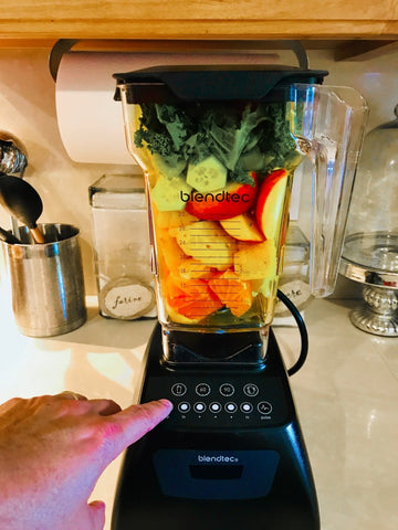 Fruit and vegetables in a blender with finger touching buttons