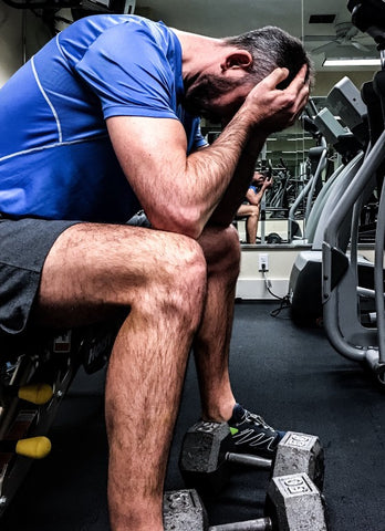 Man with mental fatigue sitting on gym bench