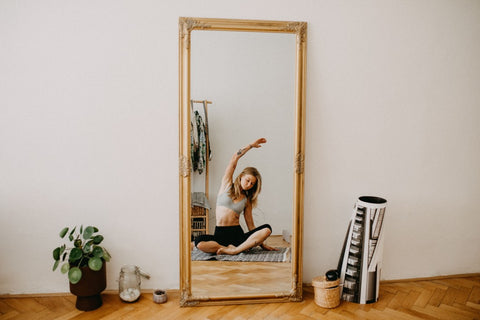 Reflection of woman in mirror doing yoga