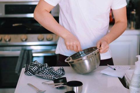 Man mixing with whisk in bowl on kitchen counter