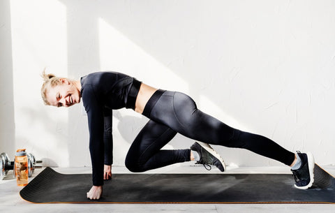 Woman with knee toughing elbow in push up position on yoga mat