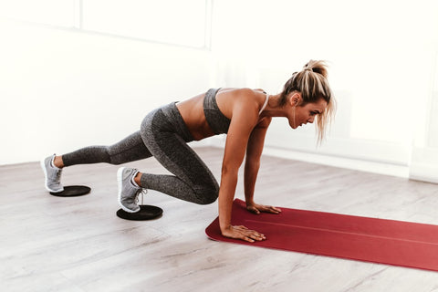 Woman with hands on end of yoga mat while doing mountain climbers