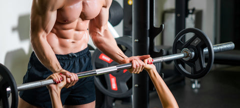 Man flexing while assisting woman benching