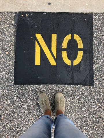 """""""No"""" sprayed on pavement in yellow"""