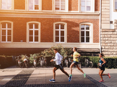 Men and women running in front of an apartment building downtown