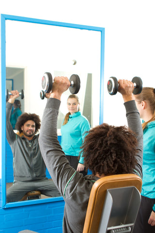 Man lifting dumbbells above head while personal trainer watches