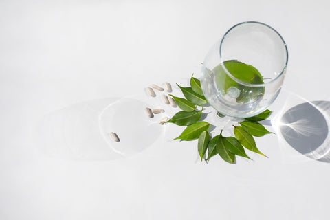 Pills and leaves next to a glass cup