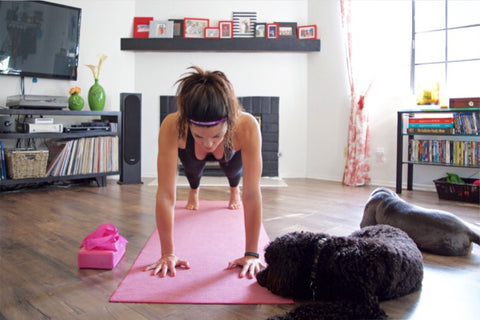 Woman holding plank on yoga mat with dogs next to her