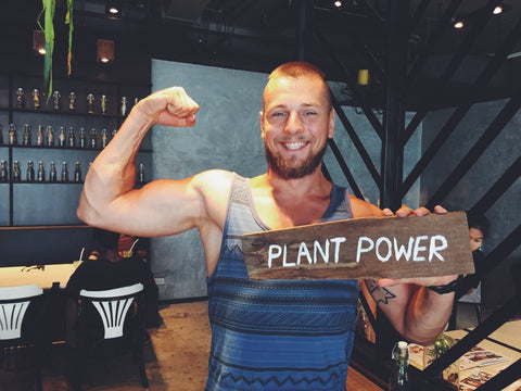 """Man flexing muscle while holding a """"plant power"""" wood sign"""