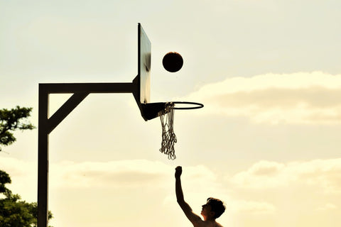 Side view of boy shooting basketball during sunset