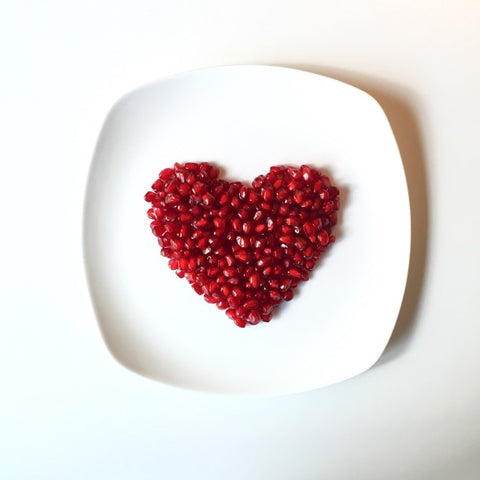 Red heart on plate made out of pomegranate
