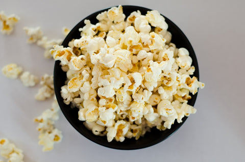 Black bowl overflowing with popcorn