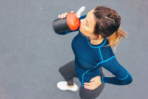 Woman with hand on hip drinking post workout protein shake