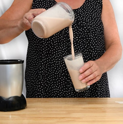 Woman pouring shake into cup from blender