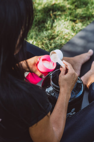 Woman pouring pre workout in a shaker bottle.