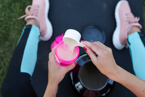 Woman putting pre workout in a shaker bottle.