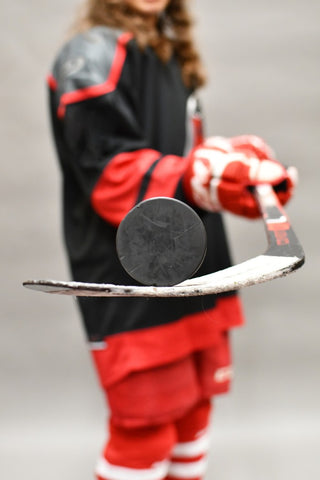 Man in background of stick with puck on it