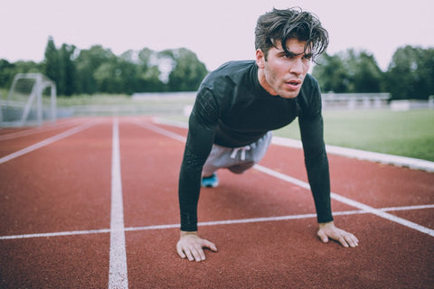 Man in push up position on track