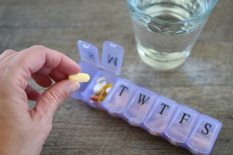 Putting BCAA pill into weekly pill container