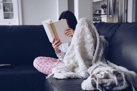 Young teenage girl sitting on a couch with a cozy blanket and reading a book
