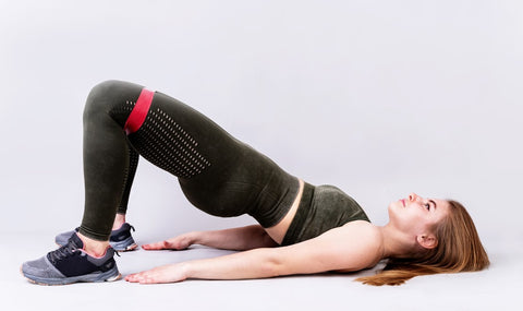 woman doing hip thrusts with resistance band