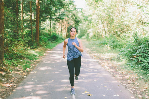 Woman running on a road surrounded by trees.