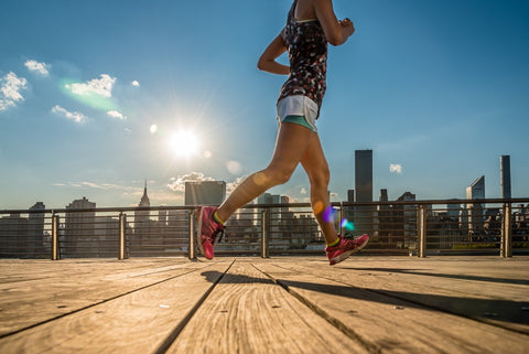Woman endurance running on a boardwalk with city in background