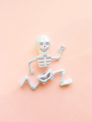Running skeleton figure in front of pink background