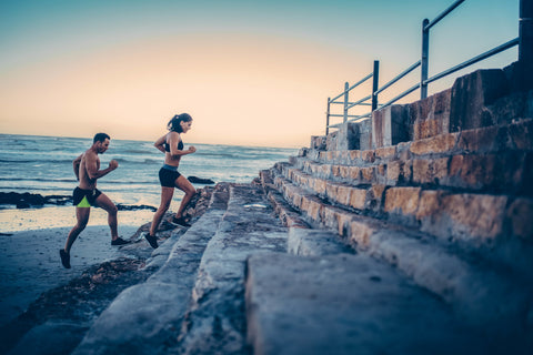 Man and woman running up stone steps with ocean in background