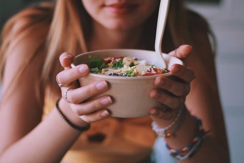 Woman holding bowl of salad close to her face