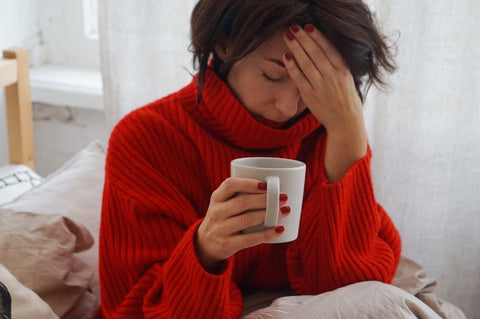 Sick woman holding a mug and rubbing her head.