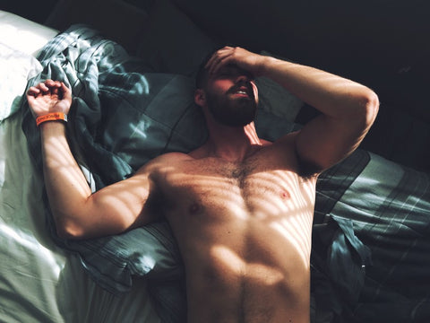 Shirtless man laying on bed with hand on forehead and eyes closed