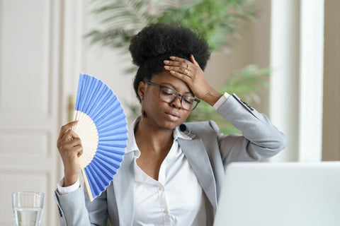 Woman in discomfort fanning herself at desk