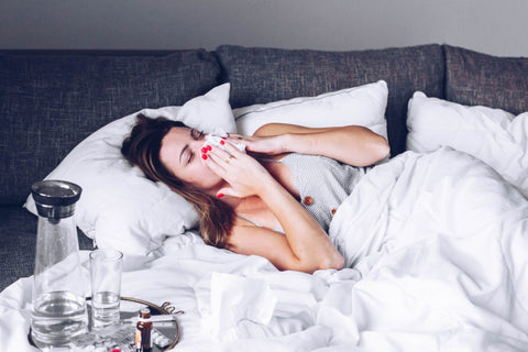 Sick woman in bed blowing nose