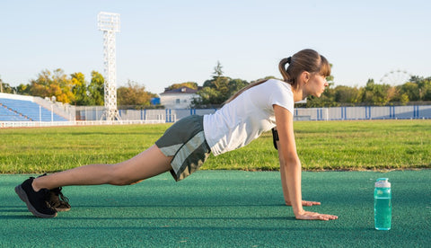 Side view of woman doing pushup on soccer field