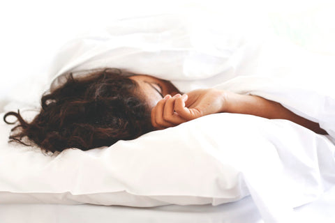 Side view of woman sleeping under covers