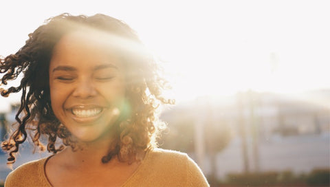 Woman smiling with sunlight in background