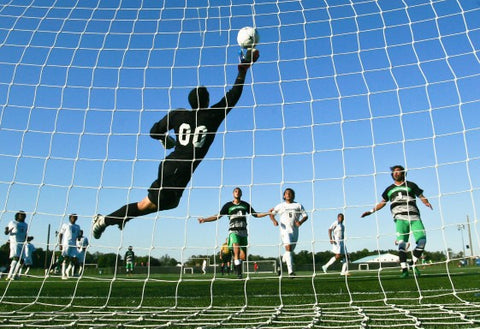 Goalie blocking goal in soccer net with players in distance