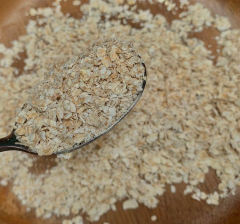 Spoon full of oats in front of pile of oats