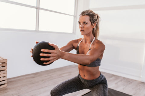 Woman squatting while holding medicine ball
