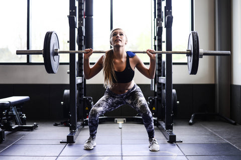 Girl looking up while squatting barbell in gym
