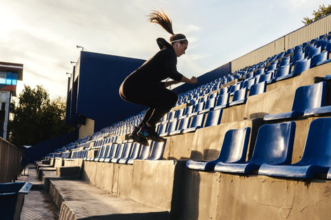 Girl jumping up stains on concrete bleachers
